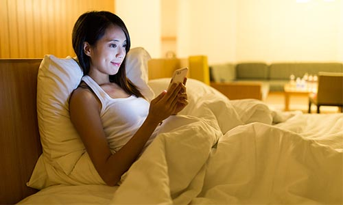 ベッドでスマホを扱う女性